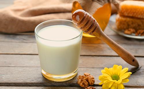 Стакан молока и мёд на деревянной столешнице