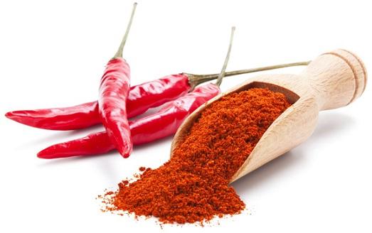 Стручки красного перца и молотый красный перец в деревянной лопатке
