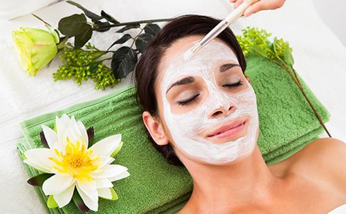 Девушке наносят белую маску на кожу лица