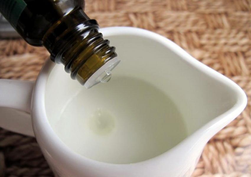 масло капает из бутылочки тёмного стекла в чашку с готовым косметическим средством