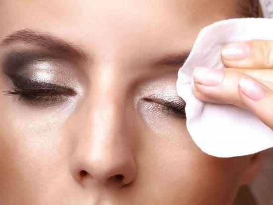 Женщина смывает косметику с глаз