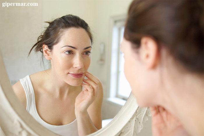 девушка-смотрит-на-свои-редкие-брови-в-зеркало