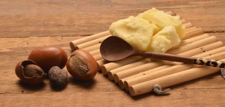 Масло ши на деревянной подставке и плоды ши на столе