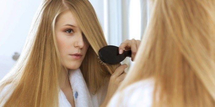 Девушка расчесывает волосы перед зеркалом